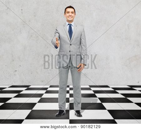business, people, gesture, partnership and greeting concept - happy smiling businessman in suit shaking hand standing on checkerboard pattern floor over gray background
