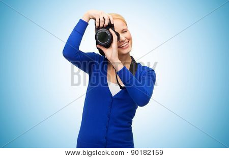 modern technology and people concept - smiling woman in casual clothes taking picture with digital camera over blue background