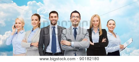 business, people, gesture and office concept - group of smiling businessmen over blue sky and clouds background
