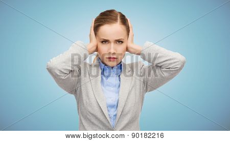 business, emotions, stress, pressure and people concept - stressed businesswoman with covered ears over blue background