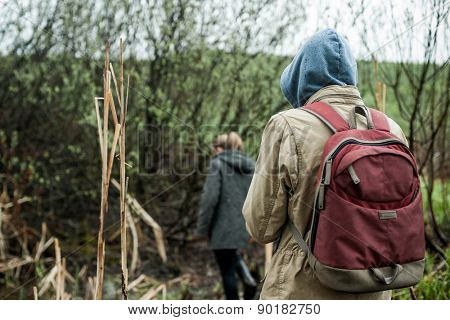 Backpacker tourists walking in rainy forest