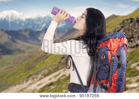 Backpacker Drinks Water On The Mountainside