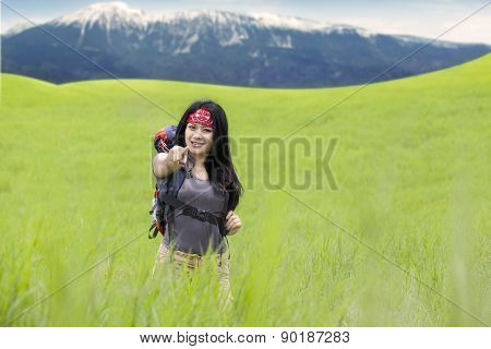 Backpacker On The Meadow Pointing At Camera
