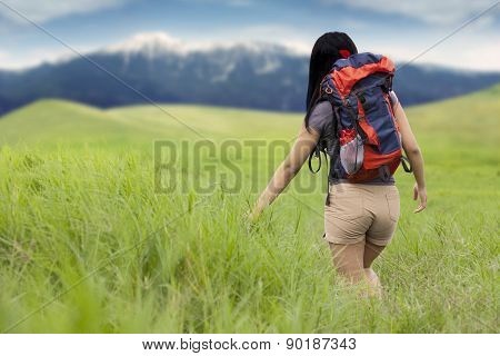 Backpacker Walking On The Meadow At Hill