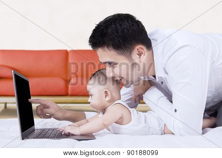 Cute Baby Using Laptop With Father