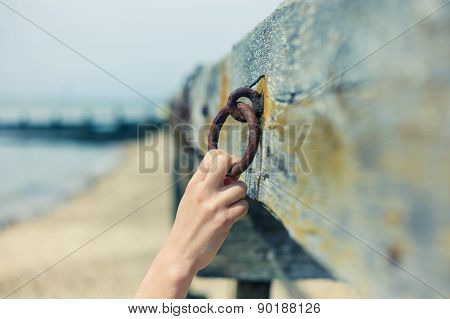 Female Hand Grabbing Rusty Chain