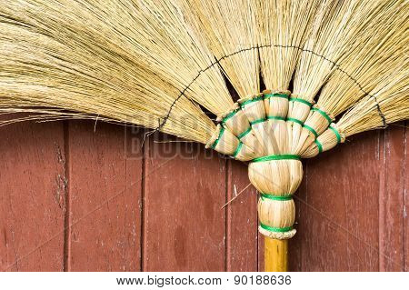 Broom Stick Lay On A Brown Wooden Door