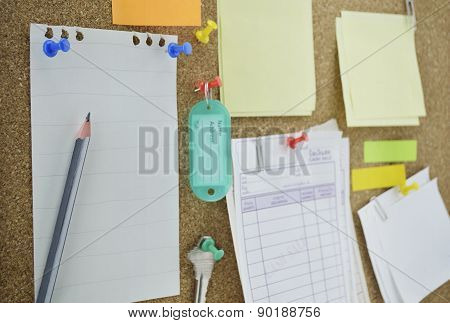 Pencil With Sticky Notes, Pin, Key And Tag Name On Cork Board
