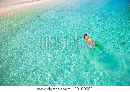 Young girl snorkeling in tropical water on vacation