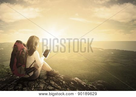 Female Hiker Using Tablet At Mountain