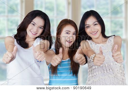 Group Of Teenage Girls Holding A Blank Board