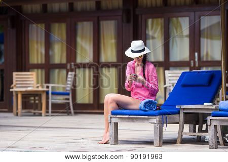 Young beautiful woman talking by phone on white beach