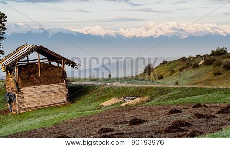 Rural Scene And High Snowy Mountain On A Background.