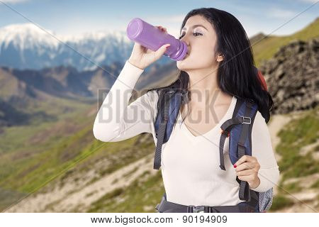 Woman Drinks Water On The Edge Of Mountain