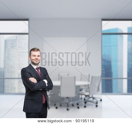 Smiling Handsome Businessman In A Black Suit With The Fold Arms. Modern Workplace In An Office.