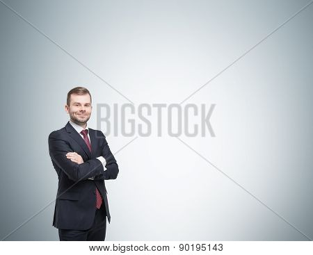 Smiling Handsome Businessman In A Black Suit With The Fold Arms. Studio Background.