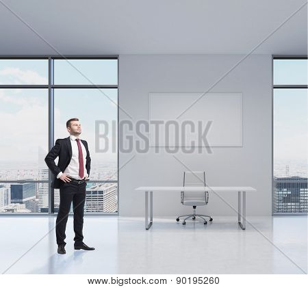 Confident Handsome Businessman Is Standing In The Modern Office In New York. Workplace With A Table