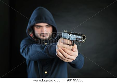 Armed Man In A Hoodie Is Pointing A Handgun At The Target.