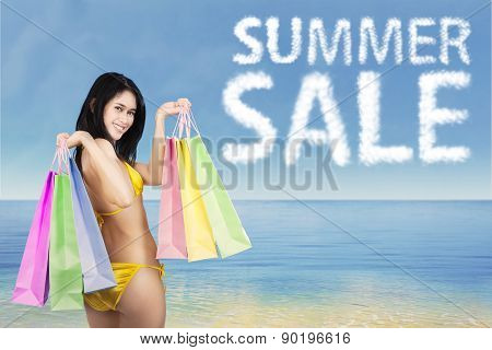 Woman With Bikini And Shopping Bags At Coast