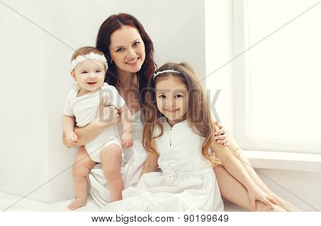 Portrait Of Happy Family, Mother Together With Two Children At Home In White Room Near Window