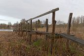 image of shaky  - Long rickety wooden bridge used to reach the small lake through the flag - JPG