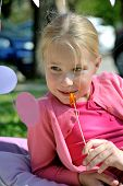 foto of eat grass  - Cute little girl sitting on green grass  and holding in hand lollipop, wearing pink dress outdoors in spring and eating sweet sugar candy, happy childhood