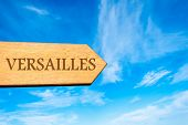 pic of versaille  - Wooden arrow sign pointing destination VERSAILLES FRANCE against clear blue sky with copy space available - JPG