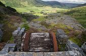 stock photo of derelict  - Looking down the welsh valley of Cwm Penmachno derelict incline drum house disused slate quarry in foreground - JPG