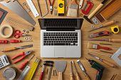 foto of handyman  - Laptop on a work table with DIY and construction tools all around top view hobby and crafts concept - JPG
