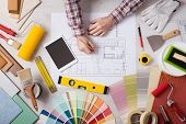 stock photo of interior decorator  - Professional decorator drawing on a house project with work tools painting rollers and color swatches all around top view - JPG