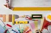 foto of interior decorator  - Decorator holding a paint brush and painting a wooden surface work tools and swatches at bottom banner with copy space - JPG