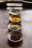 pic of bay leaf  - Dry herb served in wooden plate rosemary bay leaf black pepper turmeric - JPG