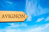 stock photo of avignon  - Wooden arrow sign pointing destination AVIGNON FRANCE against clear blue sky with copy space available - JPG