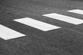stock photo of pedestrian crossing  - Pedestrian crossing road marking white rectangles over gray asphalt pavement selective focus and shallow DOF - JPG