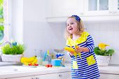 stock photo of healthy eating girl  - Little girl preparing breakfast in white kitchen - JPG