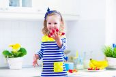 foto of healthy eating girl  - Little girl preparing breakfast in kitchen - JPG