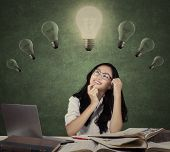 picture of clever  - Clever female student sitting in the class while thinking a solution under lightbulb - JPG