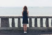 foto of balustrade  - A young woman wearing a blue dress is standing by a wall with concrete balustrades on a promenade and is admiring the seaside on a sunny day - JPG