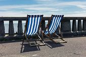 stock photo of balustrade  - Two deck chairs on a promenade by the seaside with concrete balustrades - JPG