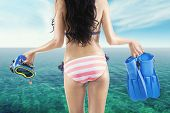 pic of flipper  - Rear view of young woman wearing bikini on the coast while holding flippers and mask for snorkeling - JPG