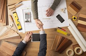 stock photo of reconstruction  - Architect and customer businessman shaking hands top view desktop with building project tools and wood swatches on background - JPG