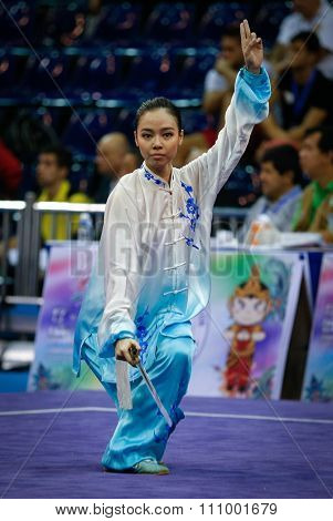 JAKARTA, INDONESIA - NOVEMBER 15, 2015: Lindswell Kwok of Indonesia performs the movements in the women's Taijijian event at the 13th World Wushu Championship 2015 held at Istora Senayan, Jakarta.