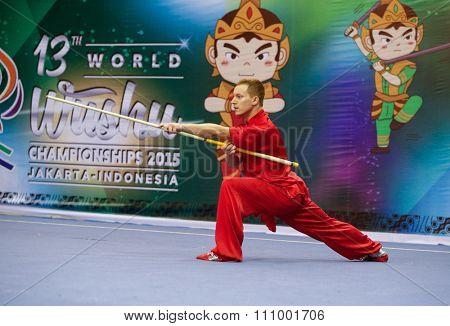 JAKARTA, INDONESIA - NOVEMBER 15, 2015: Vladimir Maksimov of Russia performs the movements in the men's Gunshu (staff) event at the 13th World Wushu Championship 2015 held at Istora Senayan, Jakarta.