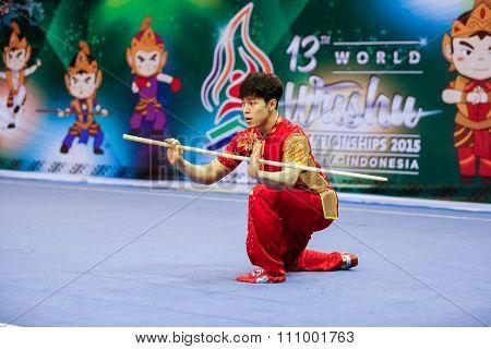 JAKARTA, INDONESIA - NOVEMBER 15, 2015: Lee Honghyun of South Korea performs the movements in the men's Gunshu (staff) event at the 13th World Wushu Championship 2015 held at Istora Senayan, Jakarta.