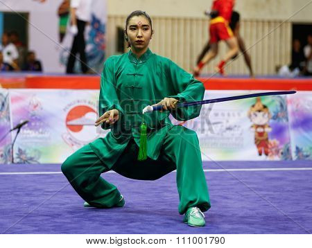 JAKARTA, INDONESIA - NOVEMBER 15, 2015: Anel Sanatkyzy of Kazakhstan performs the movements in the women's Taijijian event at the 13th World Wushu Championship 2015 held at Istora Senayan, Jakarta.
