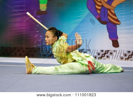 JAKARTA, INDONESIA - NOVEMBER 15, 2015: Sandi Oo of Myanmar performs the movements in the women's Qiangshu (spear) event at the 13th World Wushu Championship 2015 held in Istora Senayan, Jakarta.
