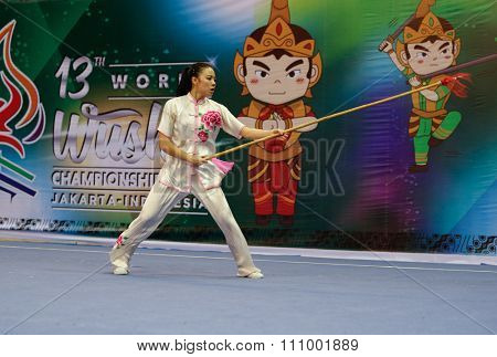 JAKARTA, INDONESIA - NOVEMBER 15, 2015: Emily Fan of the USA performs the movements in the women's Qiangshu (spear) event at the 13th World Wushu Championship 2015 held in Istora Senayan, Jakarta.
