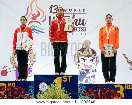 JAKARTA, INDONESIA - NOVEMBER 15, 2015: Xiaoxiao Lai of China (centre) wins the gold medal of the women's Qiangshu event at the 13th World Wushu Championship 2015 held in Istora Senayan.