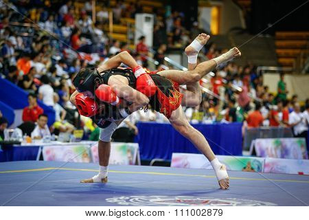 JAKARTA, INDONESIA - NOVEMBER 15, 2015: Kalil Macharaoui of Tunisia (red) fights Benabdellah Ramzi of Algeria (black) in the men's 65kg Sanda event at the 13th World Wushu Championship 2015.