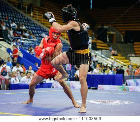 JAKARTA, INDONESIA - NOVEMBER 15, 2015: Puja Riyaya of Indonesia (red) fights Van Tai Nguyen of Vietnam (black) in the men's 70kg Sanda event at the 13th World Wushu Championship 2015 in Jakarta.